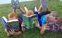 Kinderen lezen boeken op het gras